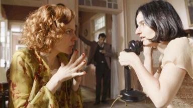 Justina segura o telefone enquanto Olga olha para ela com Zeca ao fundo em Éramos Seis