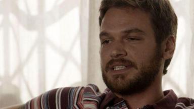O ator Emílio Dantas sentado em cena de A Força do Querer
