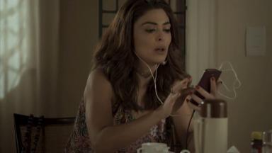 Cena de A Força do Querer com Bibi ouvindo algo no celular com fone de ouvido
