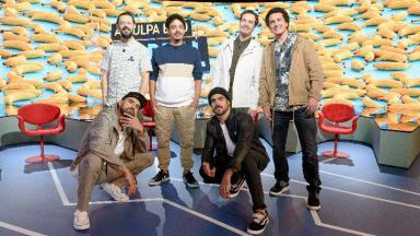 Apresentadores do A Culpa é do Cabral posados com Caio Castro no palco