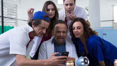"""Personagens da série """"Ala Leste"""" olhando para um celular"""