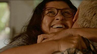 Regina Casé, como Lurdes, abraçada com seu filho em Amor de Mãe