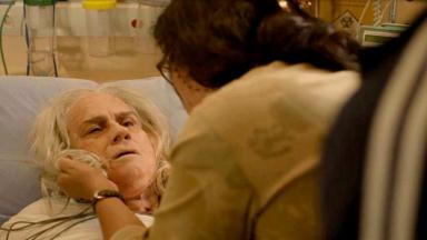 Lurdes, de costas, segura Kátia pelo colarinho enquanto ela está deitada num leito do hospital, de frente