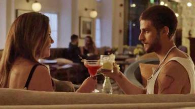 Adriana Esteves e Chay Suede frente a frente brincando, cada um segurando uma bebida.