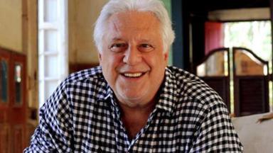 Antônio Fagundes, sentado, sorri para a câmera