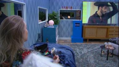 Carla Diaz sentada assistindo TV no quarto secreto do BBB21