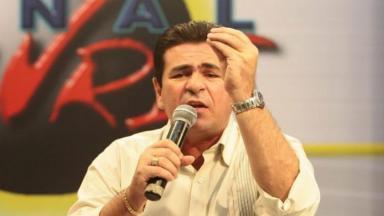 Wallace Souza segurando um microfone com a mão direita e a mão esquerda erguida, olha para a câmera