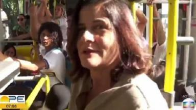 Repórter da Globo dentro de um ônibus, de pé.