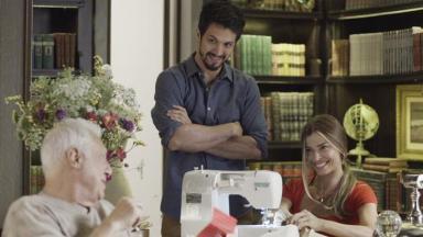 Cena de Bom Sucesso com Alberto sentado olhando para Paloma que está costurando e, Marcos de pé