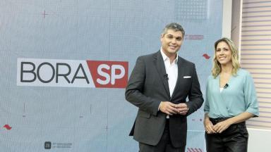 """Joel Datena e Laura Ferreira posam para foto no cenário com o logo do """"Bora SP"""""""