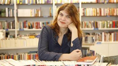 Cláudia Lage sentada em uma biblioteca, rodeada de livros.
