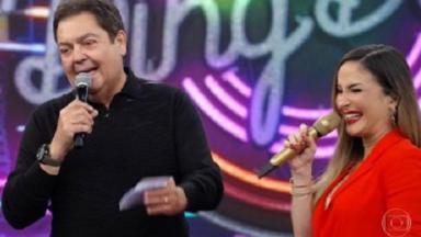 Faustão e Claudia Leitte segurando microfones e sorrindo no palco