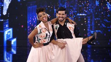 """Dandara Mariana e seu parceiro de """"Dança dos Famosos"""", ela com a perna erguida e sendo segurada por ele. Ambos sorrindo"""