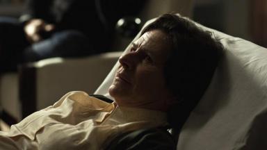 Denise Weinberg deitada num divã com olhos reflexivos