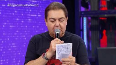 """Faustão de pé, no palco do """"Domingão"""", com o microfone, lê algo em suas anotações"""