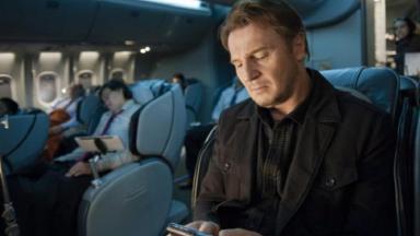 Cena do filme Sem Escala em que o protagonista está sentado na poltrona de um avião enquanto olha no celular.