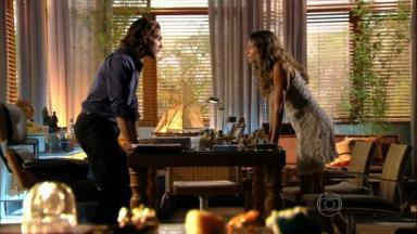 Cena de Flor do Caribe com Ester e Alberto de pe, com uma mesa entre eles, se olhando