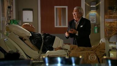 Cena de Flor do Caribe com Samuel de pé à beira da cama de Dionísio, que está deitado no hospital