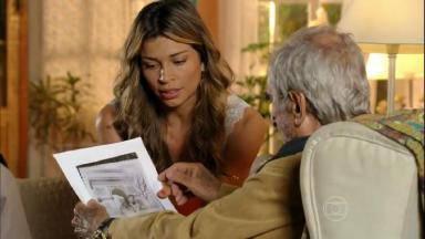 Cena de Flor do Caribe com Ester mostrando uma foto para Manolo