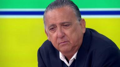 Galvão Bueno sentado com cara de desânimo.