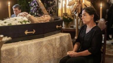 Lola sentada numa cadeira ao lado do caixão de Júlio durante o velório em Éramos Seis