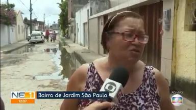 Mulher sendo entrevistada em uma rua. Ao fundo, outra mulher presa num portão automático