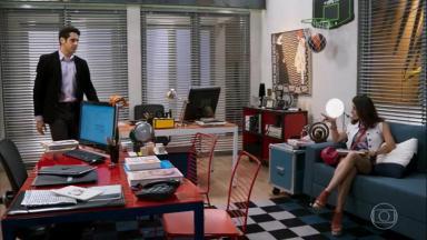 Cena de Haja Coração com Carmela sentada no escritório e Beto entrando