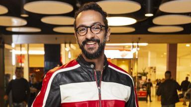 Irandhir Santos, sorrindo, de pé, posa para foto