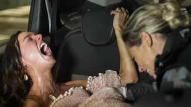 Deitada no banco traseiro do carro, Ritinha grita de dor enquanto que Jeiza faz o parto
