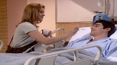 Cena de Laços de Família, com Edu deitado na cama do hospital e Camila dando sorvete na boca dele