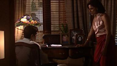 Cena de Laços de Família com Edu sentado numa cadeira e Alma de pé, ao lado dele