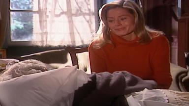Cena de Laços de Família com Helena sentada à beira da cama de Aléssio