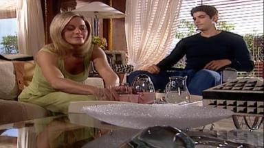 Helena sentada pegando água para Edu, que está sentado ao lado dela