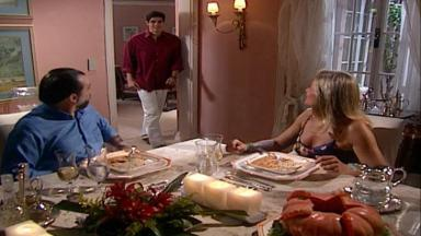 Cena de Laços de Família com Helena e Miguel jantando e Edu em pé ao lado