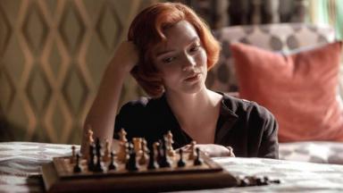 Cena de O Gambito da Rainha com a protagonista sentada no chão vendo um tabuleiro de xadrez