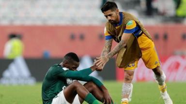 Jogador do Palmeiras sentado no gramado e do Tigres o cumprimentando