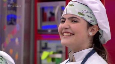 Raphaela Alvitos vestida de chef de cozinha, sorrindo após o anúncio de que ela venceu o Super Chefinhos