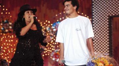 Regina Casé segura um microfone enquanto Tiago Martins ao seu lado, segura um buquê de flores
