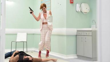 Sophia, protagonista de Topíssima, segurando uma arma enquanto há um homem caído