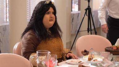 Camila Rodrigues caracterizada como Sophia muito gorda e comendo sentada numa mesa
