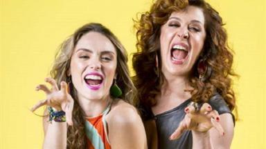 Isabelle Drummond e Cláudia Raia caracterizadas como Manuzita e Lidiane em Verão 90, posam para foto sorrindo e imitando a pantera