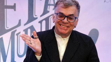 Walcyr Carrasco posa foto com a mão direita erguida e sorrindo