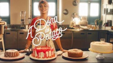 """Juliana Paes caracterizada com boleira, numa cozinha, com vários bolos na sua frente. E o logo de """"A Dona do Pedaço"""" na tela"""