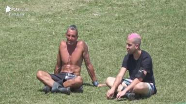 Na área externa, Juliano Ceglia conversa com Lucas Maciel enquanto eles estão sentados no pasto de A Fazenda 2020
