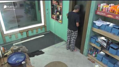 Na área fora do banheiro, Lucas Maciel faz xixi na porta do cômodo em A Fazenda 2020