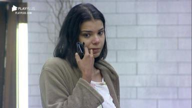 Jakelyne Oliveira séria com óculos na mão e dedo na boca