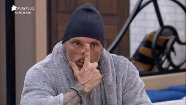 Juliano Ceglia com o dedo no nariz e touca