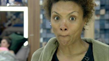 Lidi Lisboa fechando a boca, em frente ao espelho do quarto