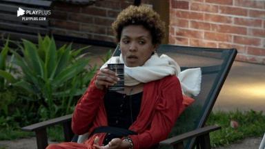 Lidi Lisboa sentada na área externa, irritada, segurando um copo