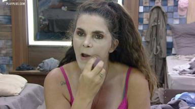 Luiza Ambiel tenta remover maquiagem exagerada diante do espelho do quarto